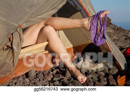 A Woman\'s Naked Legs Hold A Pair Of Lingerie Outside Of A Tent On A Mountain
