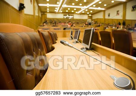 Conference halls with magnificent leather armchairs and wooden tables with microphones and monitors, Close up