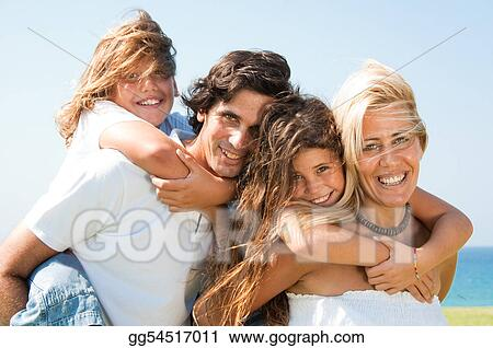 Couple giving children piggyback rides smiling