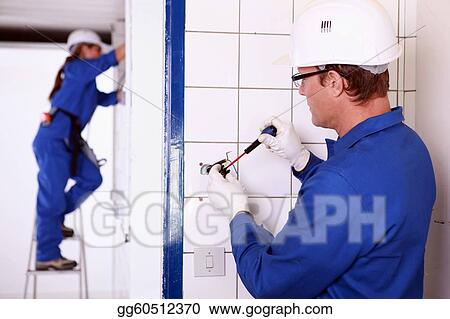 Electricians wiring a white and blue building
