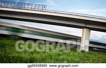 fast train going swiftly through summer landscape and passing under a highway bridge