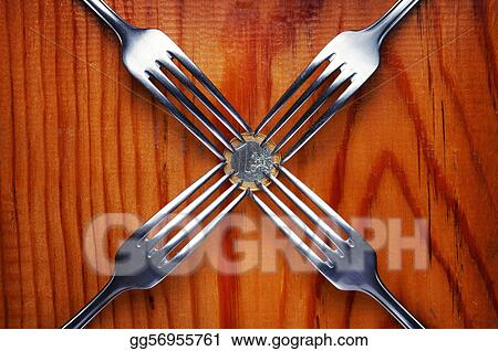 Four forks fighting over one euro coin , financial crisis competition ,wood background