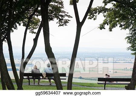 Old age and youth concept: a senior and a young couple enjoying a lovely view of the landscape