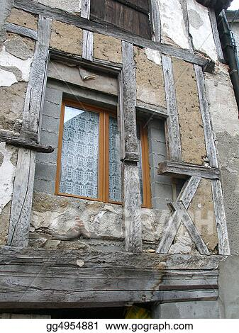 Old and New. An inner wall and modern window behind a half-timbered facade. Beaulieu-sur-Dordogne, Limousin, France.       