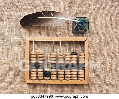 old glass inkwell with a quill pen and abacus on wooden table