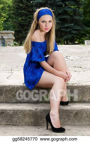 Pretty young woman in blue dress sitting outdoors