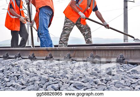 railway embankment, rails and workers in orange vests