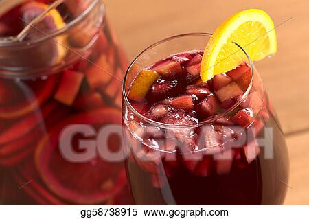 Refreshing red wine punch called sangria mixed with orange, apple, mango pieces served in wine glass garnished with orange slice on the rim (Selective Focus, Focus on the front of the orange slice gar