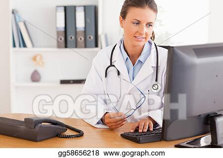 Serious female doctor working with a computer