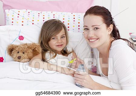 Sick little girl in bed taking cough medicine