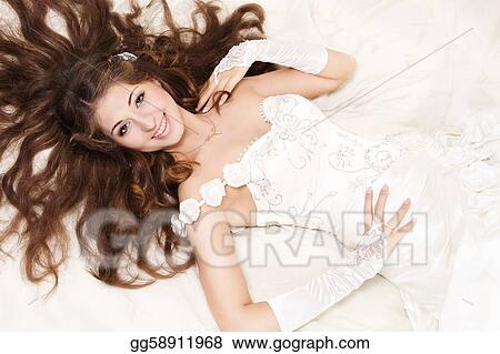 Smiling bride with curly long hair lying over white. High angle view. Fashion wedding shoot.