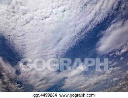 The dark blue sky with cumulus clouds