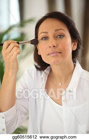 Thirty years old woman applying blush