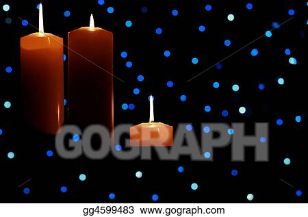 Three large candles lit amongst blue lights