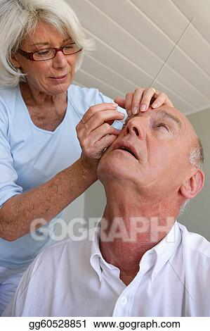 Woman helping husband with contact lenses