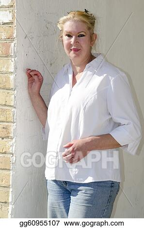 Woman in her 50s leans against a wall