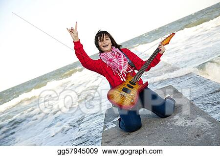 Young brunet girl play on guitar at sea pier in wind day.