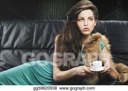young elegant lady laying down on sofa keeping and drinking from a little cup of coffee. wearing green dress. she is lying on the sofa, looks at the left and takes the cup with both hands.