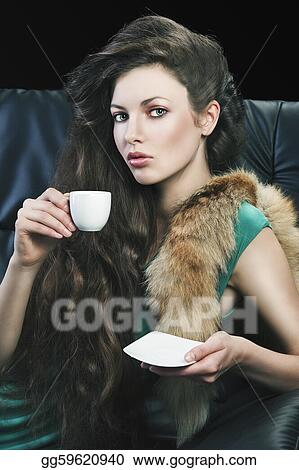 young elegant lady laying down on sofa keeping and drinking from a little cup of coffee. wearing green dress. She looks in to the lens, with right hand takes the cup and has saucer in left hand.