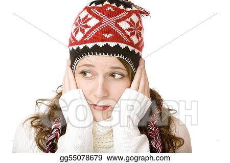 Young woman is freezing and wearing a cap and a scarf with hands in her face. Isolated on white.