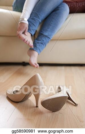 Young woman sat at home rubbing her feet after taking off her high heels