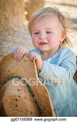 18b5218e1ca Stock Photograph - Adorable baby girl with cowboy hat at the pumpkin ...