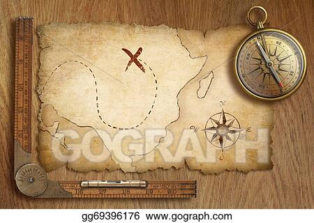 aged treasure map ruler and old gold compass on wooden table to