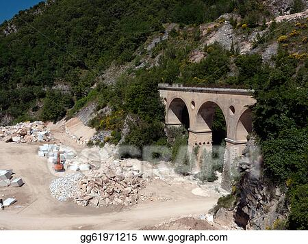 Stock Image - Carrara marble quarry with digger excavator
