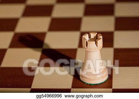 Picture - Chess piece - a white rook on a chessboard  Stock