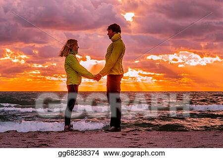 Pictures - Couple man and woman in love standing on beach