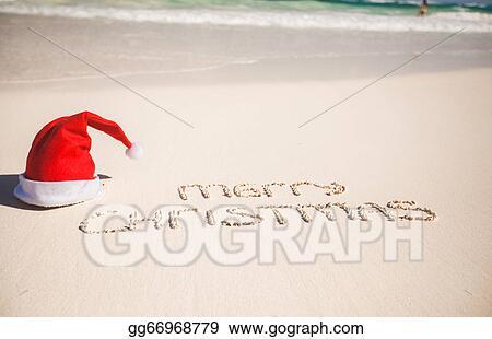 f85dbf85e75e8 Picture - Santa hat on white sandy beach and merry christmas written ...