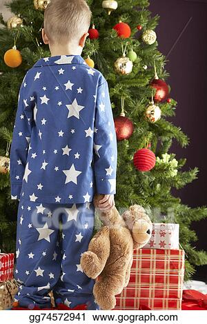 a98a15d238 Picture - Young boy holding teddy bear in front of christmas tree ...