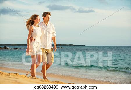stock photos young couple in love walking on the beach at sunset